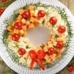 Holiday Cheese Wreath ~ this easy and festive Christmas party appetizer is made by arranging cubes of cheese in a ring, accenting with cherry tomatoes and a garland of rosemary, and finishing off with a bell pepper bow! | FIveHeartHome.com