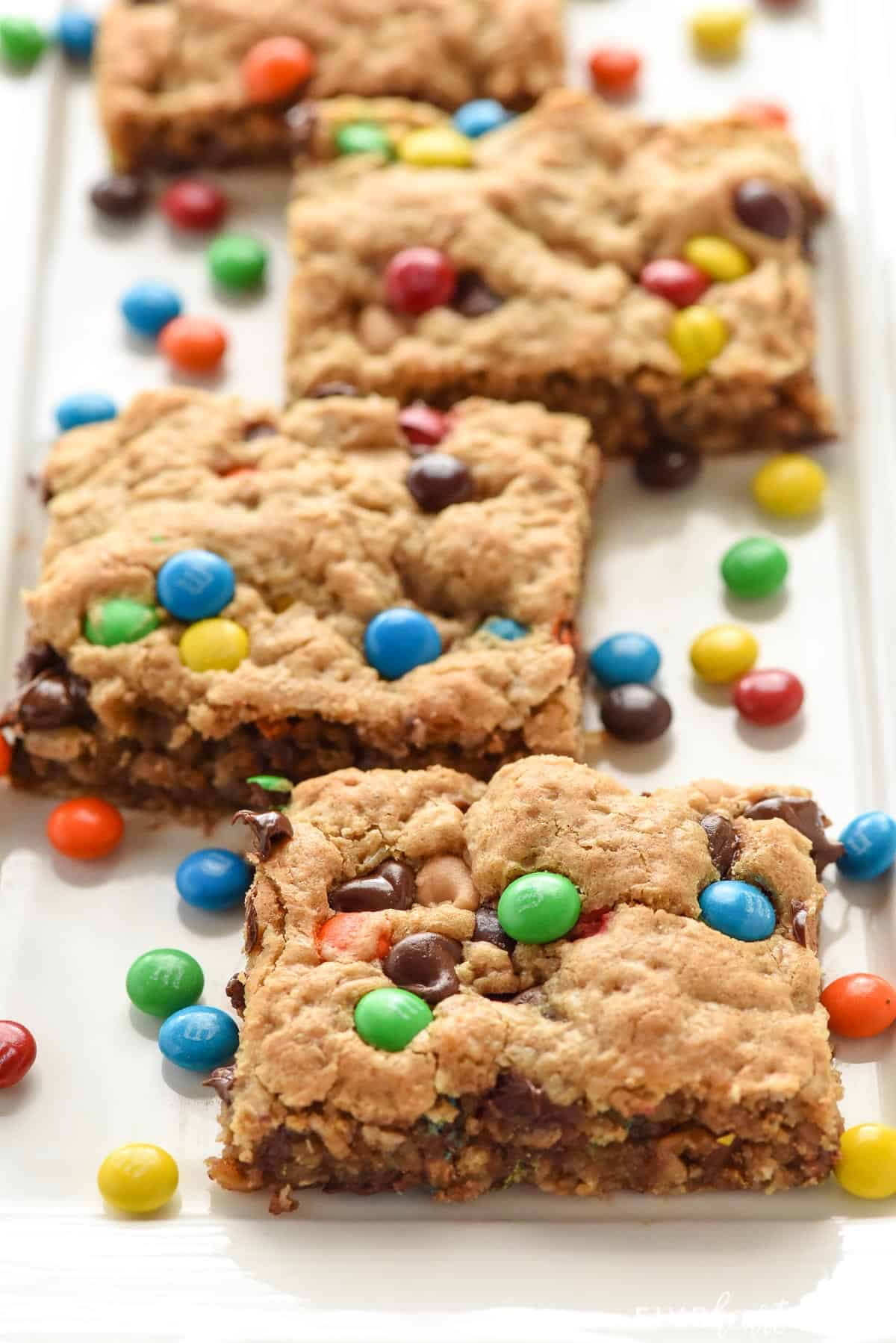 Monster Cookie Bars on white platter with mini M&Ms.