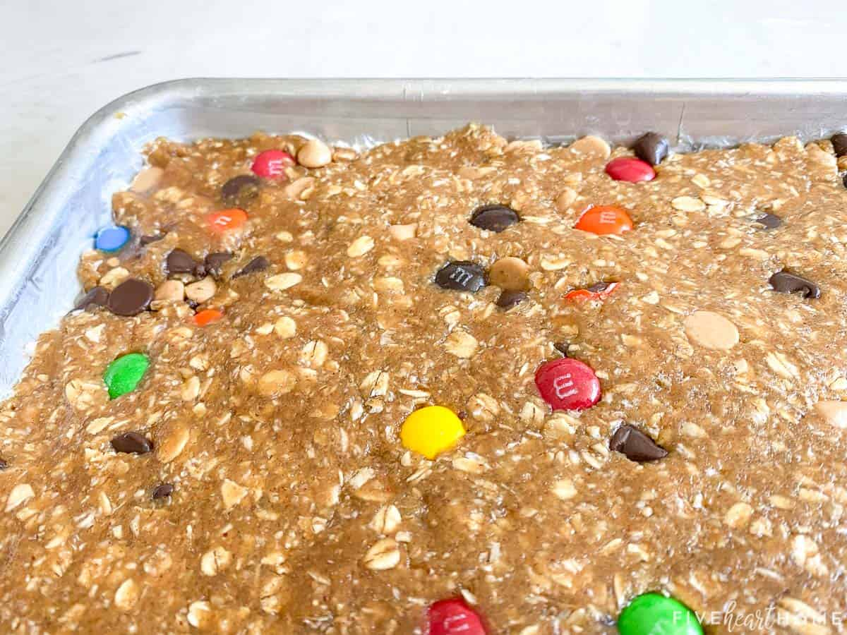 Monster Cookie Bars dough pressed into sheet pan.