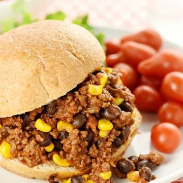 Taco Sloppy Joe sandwich on a plate with grape tomatoes on side