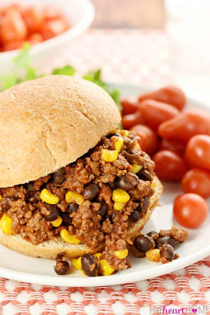 Taco Sloppy Joes filling in a sandwich on a plate with tomatoes on the side
