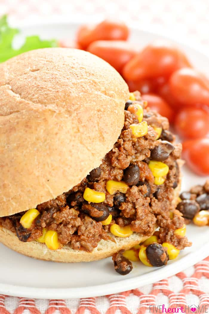Close-up of sandwich on plate with ground beef, black beans, and corn spilling out of the bun