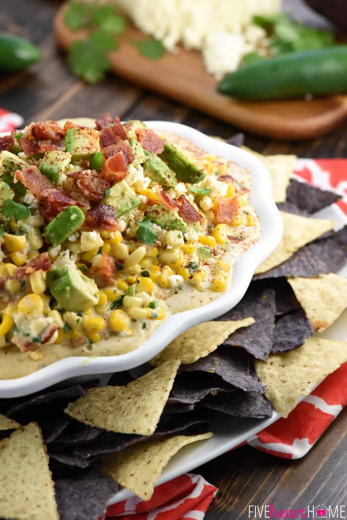 Ultimate Mexican Street Corn Dip ~ warm, creamy, and loaded with a mouthwatering combo of ingredients...corn, cotija cheese, avocado, bacon, jalapeños, cilantro, and chipotle chile powder for the perfect amount of smoky heat...ideal for Super Bowl, game day, or just about any party or get-together! | FiveHeartHome.com