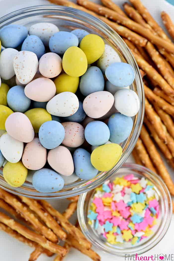 Bowl of Cadbury Mini Chocolate Eggs, pretzel sticks, and star-shaped pastel sprinkles