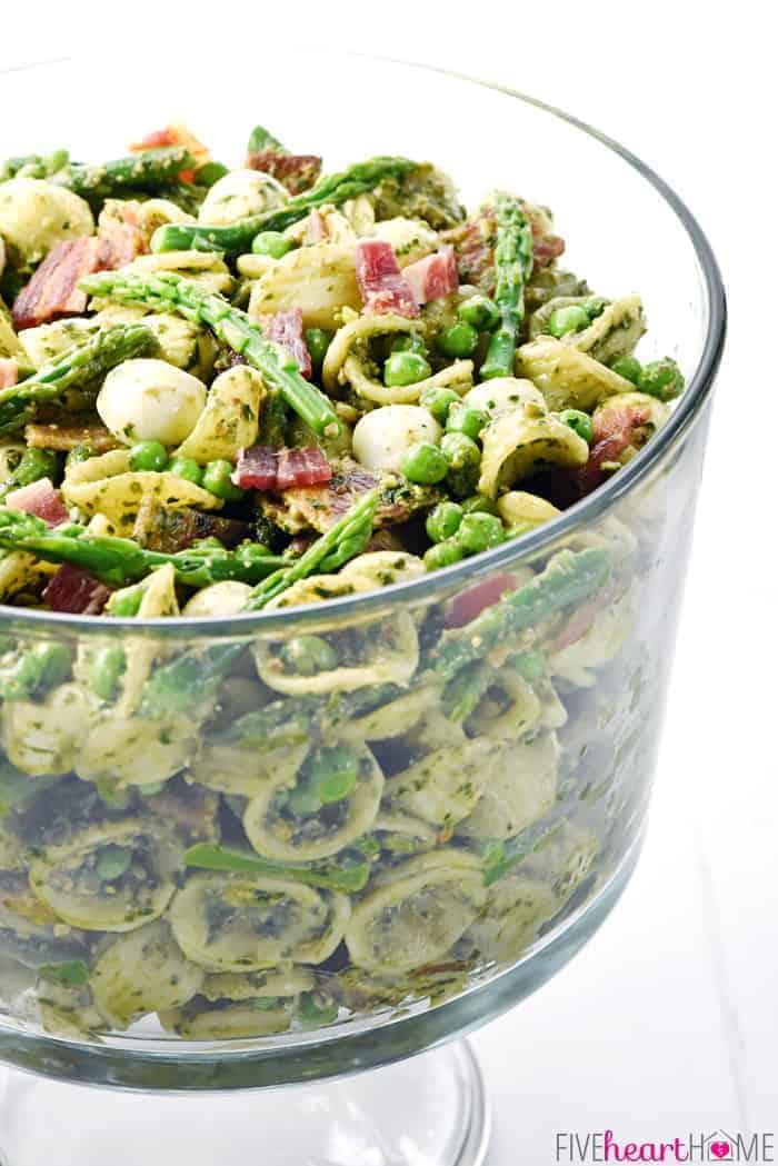 Side view of Pesto Pasta Salad in glass pedestal bowl.