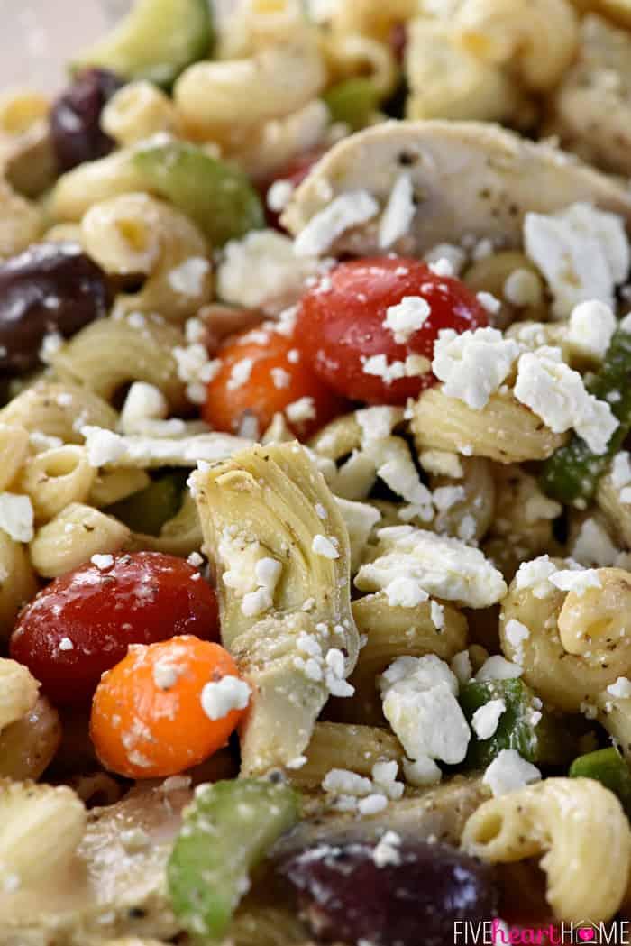 Zoomed shot of ingredients in Greek Pasta Salad, including chicken, artichokes, tomatoes, olives, and feta