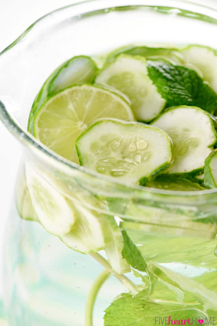 Cucumber Water with mint, limes, and cucumber slices floating in pitcher.