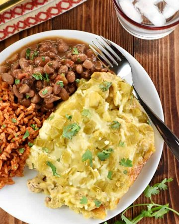 Aerial view of Chicken Enchilada Casserole on plate with rice and beans.