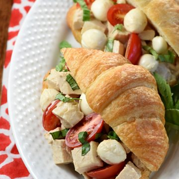 Aerial view of Caprese Chicken Salad in croissants on plate.