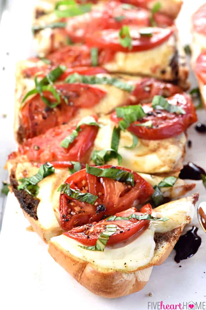 Caprese French Bread Pizza ~ this bursting-with-flavor recipe is brushed with garlic-infused olive oil, layered with fresh mozzarella and thinly-sliced tomatoes, and baked until bubbly before getting finished off with ribbons of basil and a balsamic reduction! | FiveHeartHome.com
