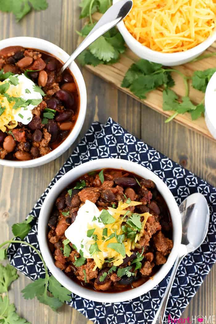 Slow Cooker Beefy Three-Bean Chili ~ a chunky, hearty, flavorful bowl of crock pot comfort food goodness, easy to adjust to your preferred spice level and delicious topped with sour cream, shredded cheese, and fresh cilantro! | FiveHeartHome.com