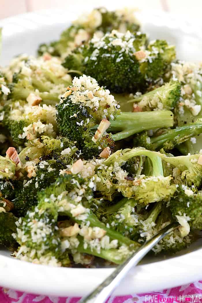 Close-up of Roasted Broccoli in a serving dish, topped with Parmesan, breadcrumbs, and pecans