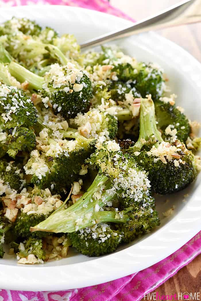 Close-up of serving dish of Parmesan Roasted Broccoli on pink cloth with spoon