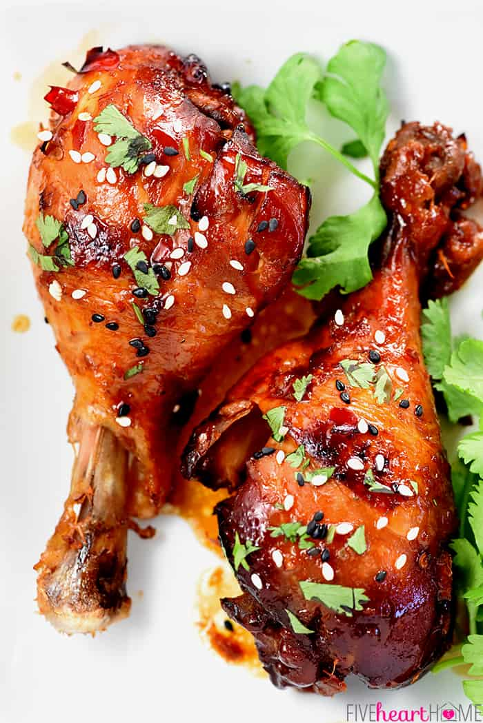 Aerial shot of two Crockpot Chicken Drumsticks sprinkled with sesame seeds and cilantro