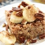 Banana Baked Oatmeal on a plate garnished with sliced bananas, toasted pecans, and cinnamon