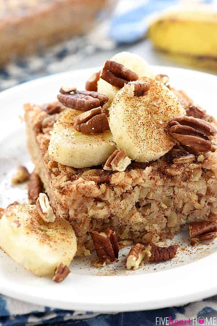 Serving of Banana Baked Oatmeal on a plate with pecans and sliced bananas.