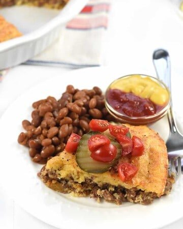 Cheeseburger Pie on a plate with garnishes.