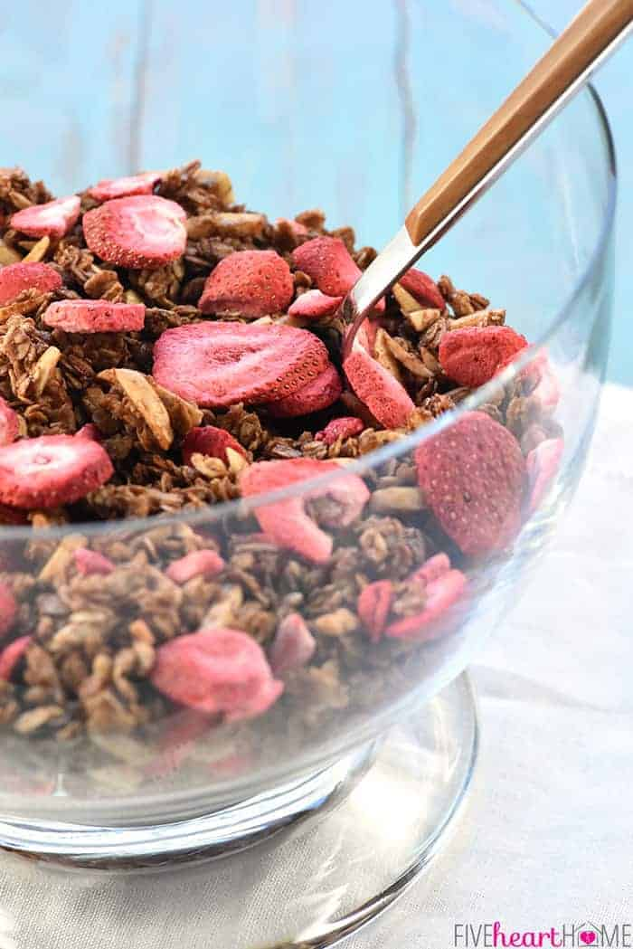 Big glass bowl of Strawberry Granola with a serving spoon