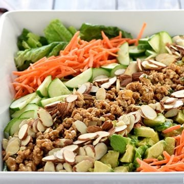 P.F. Chang's Chicken Lettuce Wraps Salad ~ transforms the popular restaurant appetizer into a savory main dish salad, loaded with copycat ground chicken filling, shredded carrots, sliced cucumbers, diced avocado, toasted almonds, and an Asian-inspired Sesame Ginger Vinaigrette! | FiveHeartHome.com