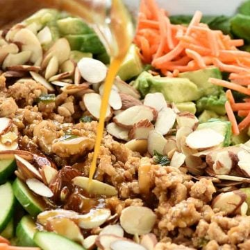 Dressing being poured over P.F. Chang's Chicken Lettuce Wraps Salad