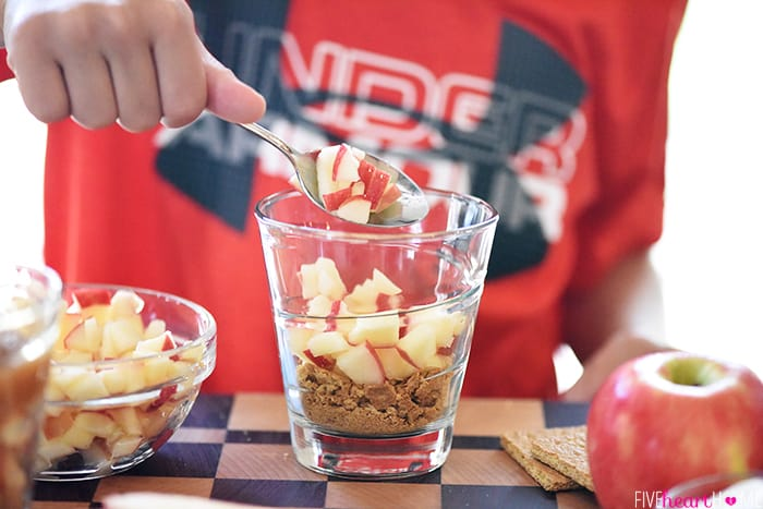 Healthy Apple Pie Snack Cups ~ layers of graham cracker crumbs, diced apples, cinnamon applesauce, and whipped cream make a wholesome after-school snack or dessert that tastes just like apple pie! | FiveHeartHome.com