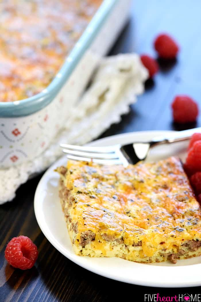 Close-up of Breakfast Casserole on plate with fork and raspberries scattered on table