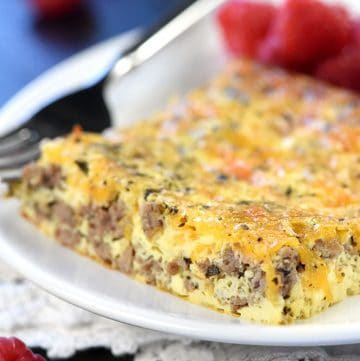Slice of beef and cheese breakfast casserole on a plate with raspberries