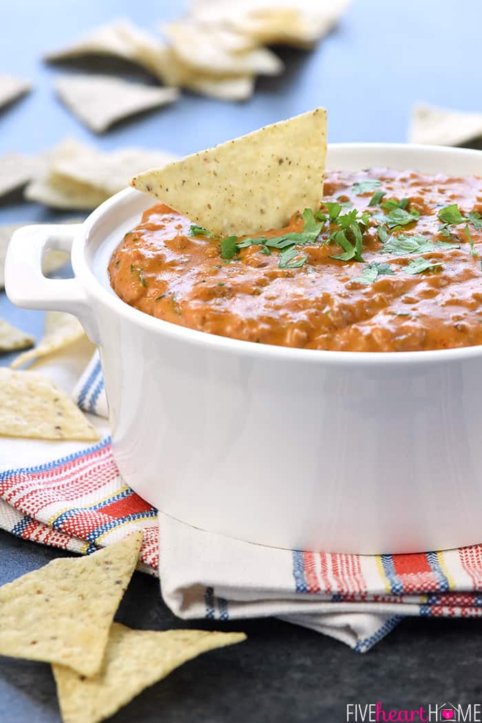 Hot Taco Dip in white serving dish with tortillla chip dipping into it.