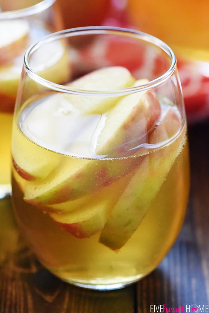 Sparkling Honeycrisp Apple Cider Sangria ~ a festive fall cocktail recipe with only three ingredients -- white wine, apple cider, and sweet sliced apples -- perfect for tailgating, Halloween, Thanksgiving, and even Christmas! | FiveHeartHome.com