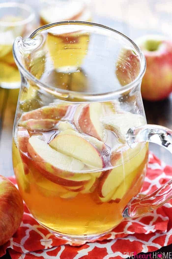 Sparkling Apple Cider Sangria Recipe ~ a festive fall cocktail made with only three ingredients -- white wine, apple cider, and sweet sliced Honeycrisps -- perfect for tailgating, Halloween, Thanksgiving, and even Christmas! | FiveHeartHome.com