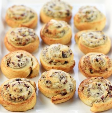 White serving tray of Blue Cheese Cranberry Pecan Crescent Pinwheels.