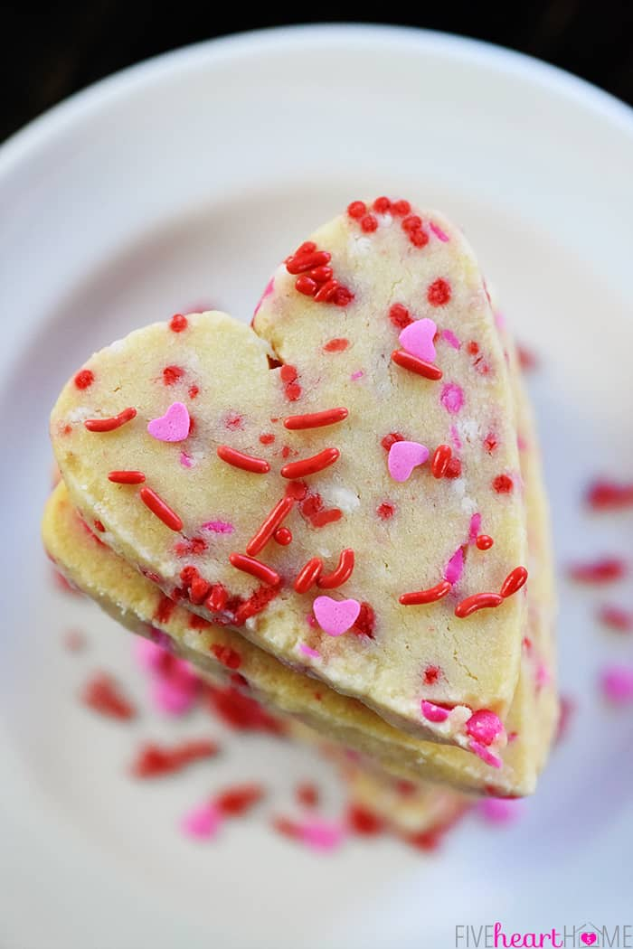 Aerial view of stack of heart shaped cookies with sprinkles.