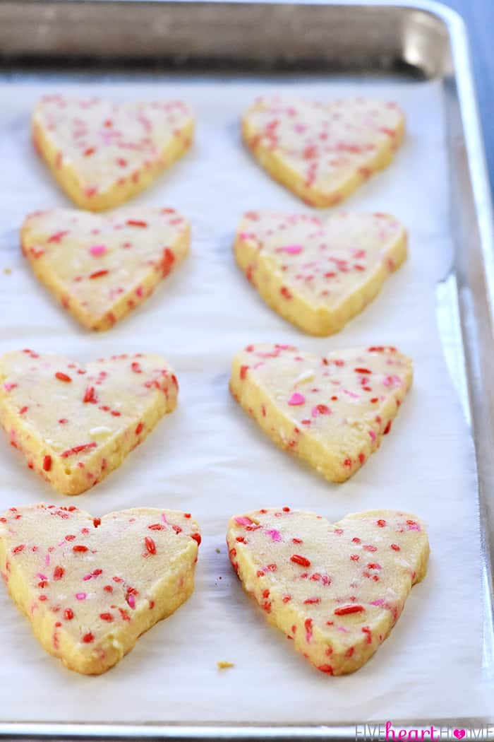 Baking sheet of heart cookies fresh out of the oven.