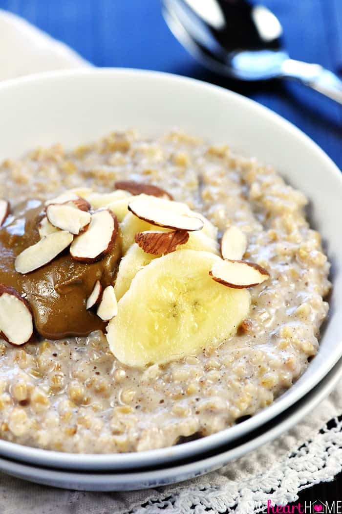 Bowl of oatmeal topped with bananas, peanut butter and slivered almonds