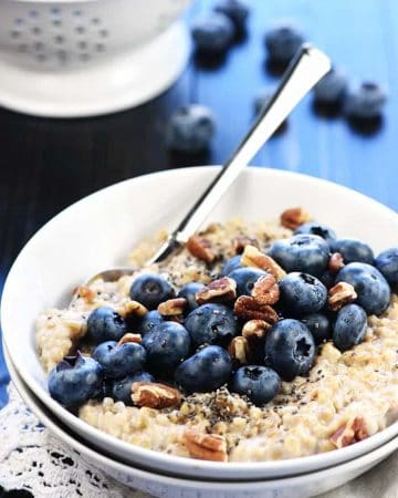 Steel cut oats in bowl with fresh blueberries and pecans.