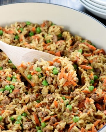 One-Pan Asian Ground Beef and Rice recipe in skillet with wooden spoon.