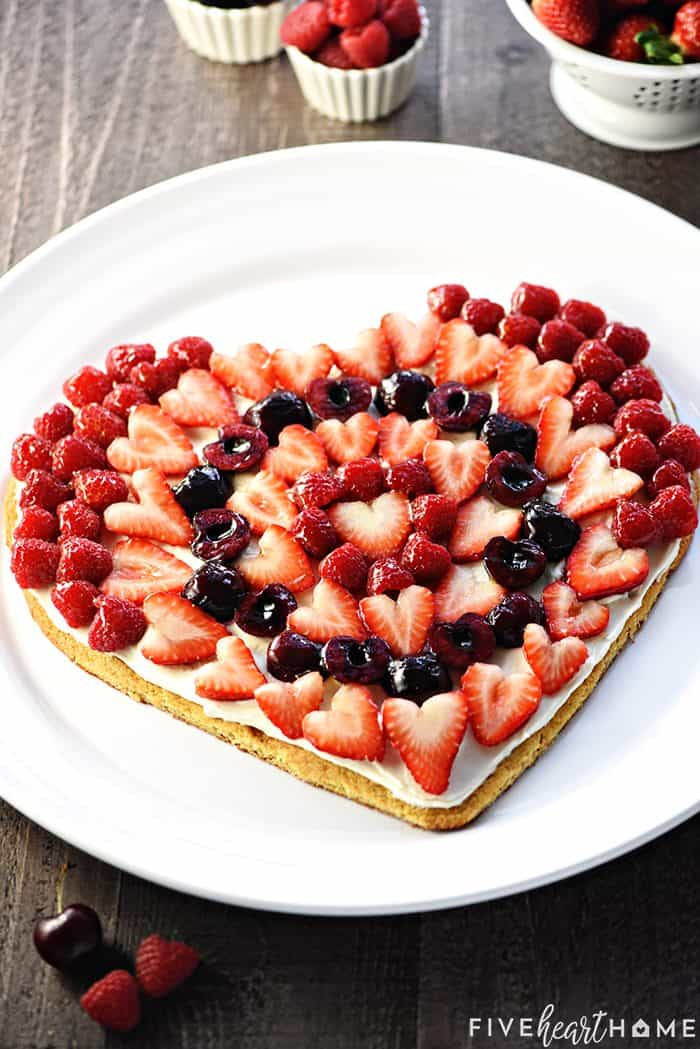Valentine's Day Fruit Pizza ~ featuring a tangy cream cheese frosting on a heart-shaped sugar cookie crust topped by sweet, glossy berries and cherries, this is the perfect Valentine's Day dessert recipe! | FiveHeartHome.com