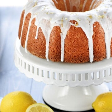 Lemon Pound Cake on cake stand with fresh lemons on table.