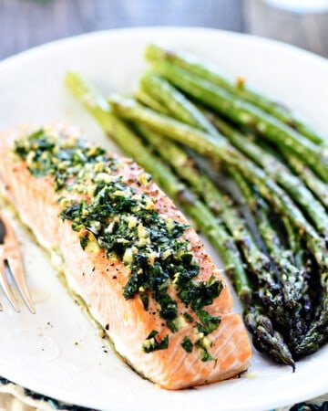 Oven Baked Salmon with Garlic and Parsley on plate with asparagus.