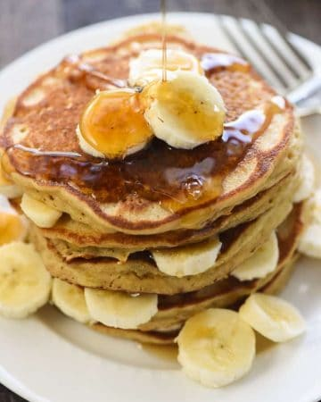 Perfect Whole Wheat Banana Pancakes ~ scrumptious and wholesome, these pancakes are light and fluffy with crisp, golden edges and delicious banana flavor. And nobody will ever guess that this amazing banana pancake recipe is made with 100% whole wheat flour! | FiveHeartHome.com