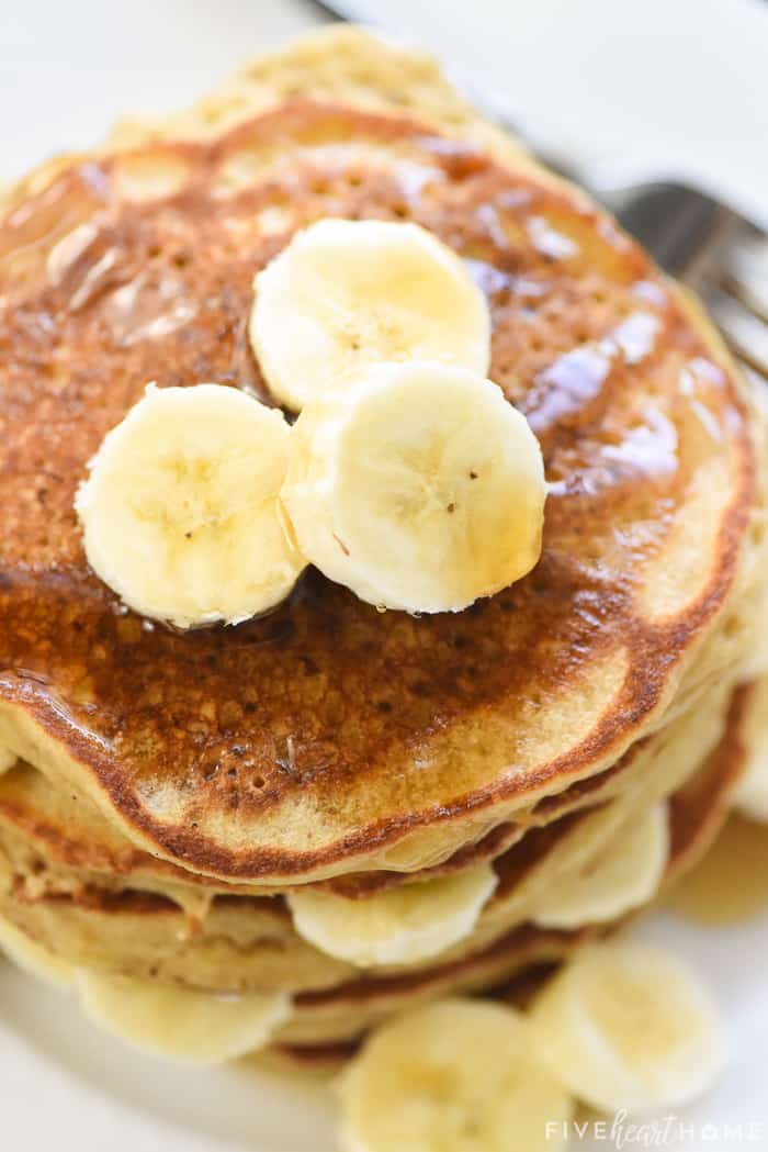 Healthy Banana Pancakes in a stack with syrup and bananas on top