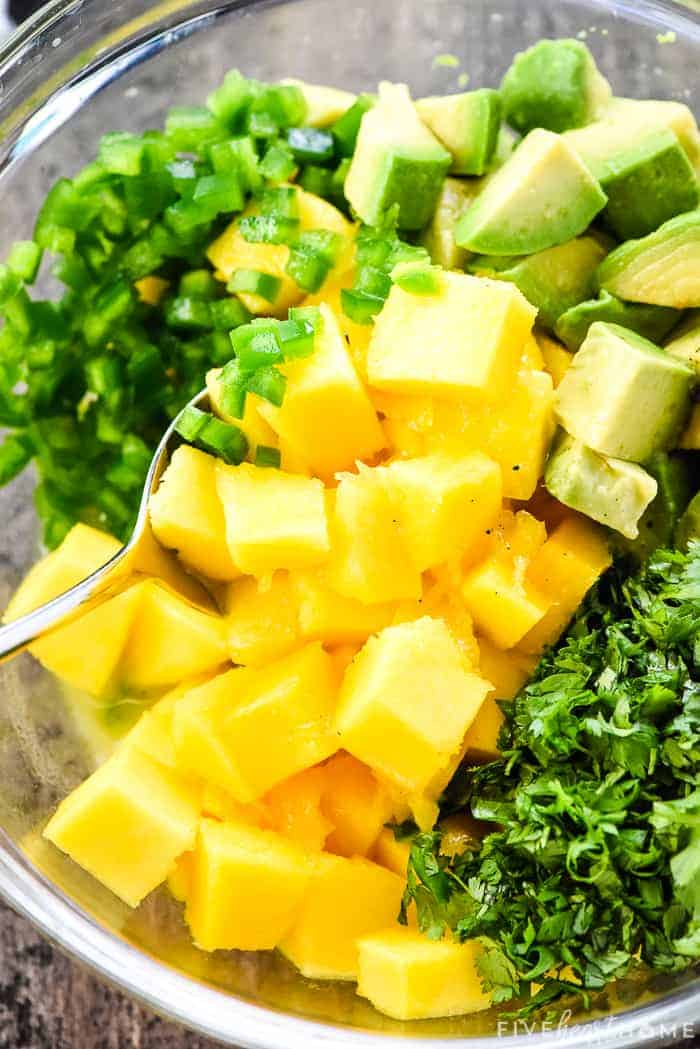 mango, avocado, jalapeño, cilantro, and lime dressing being stirred together in a bowl