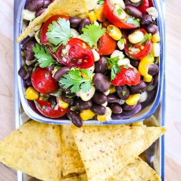 Black Bean and Corn Salad with Tomatoes + Cilantro ~ an easy, zesty, addictive recipe with a garlicky lime vinaigrette that's delicious as a side salad or dipped up with chips! | FiveHeartHome.com #blackbeancornsalad #summersalads #blackbeansalad #cornsalad #tomatosalad