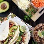 Aerial shot of Slow Cooker Pork Tacos plus garnishes.