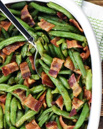 Aerial view of Green Beans with Bacon in a serving dish with spoon.