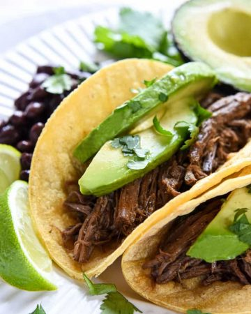 Slow Cooker Barbacoa ~ a delicious addition to tacos, burritos, rice bowls, salads, and more...and this easy, succulent, crockpot version is bursting with chipotles, garlic, cilantro, & Mexican spices! | FiveHeartHome.com
