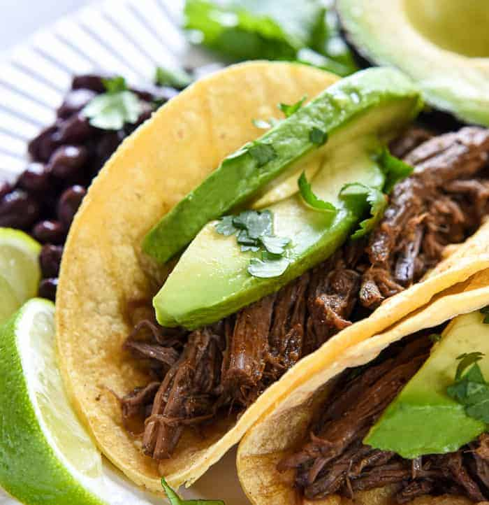 Slow Cooker Barbacoa ~ a delicious addition to tacos, burritos, rice bowls, salads, and more...and this easy, succulent, crockpot version is bursting with chipotles, garlic, cilantro, & Mexican spices!   FiveHeartHome.com