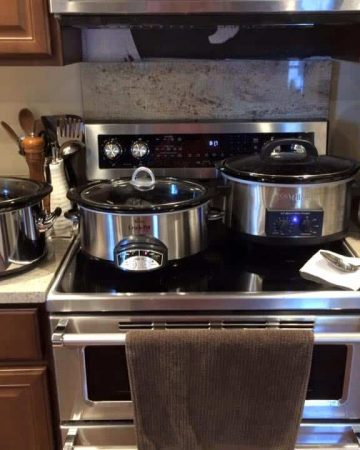 Three slow cookers lined up on kitchen counter and stovetop next to coffee pot