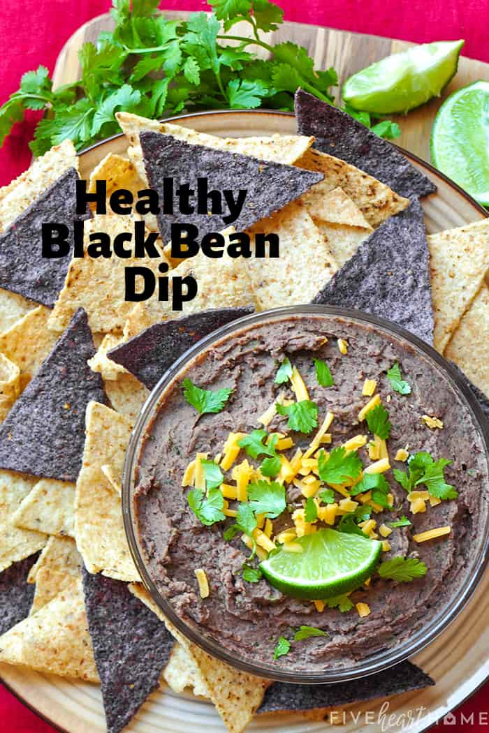 "Aerial view of bowl of black bean dip, garnished with cilantro, shredded cheddar, and a lime wedge, surrounded by yellow and blue corn tortilla chips. Text overlay reads ""Healthy Black Bean Dip"""