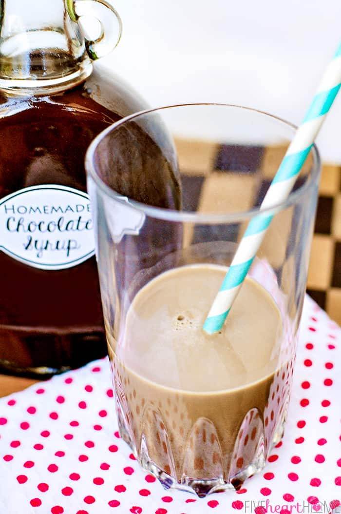 Glass of chocolate milk with a blue and white striped straw and bottle of syrup in background